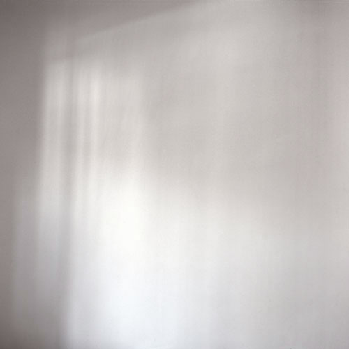 Photograph of soft vertical shadows on white wall.